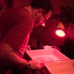 Papel salgado sendo pós-processado sob luz vermelha.